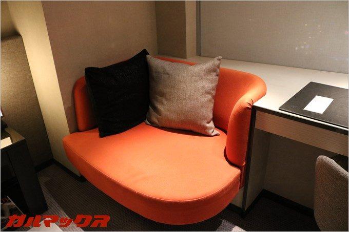 2人で寛げるオレンジのソファーが設置されています。